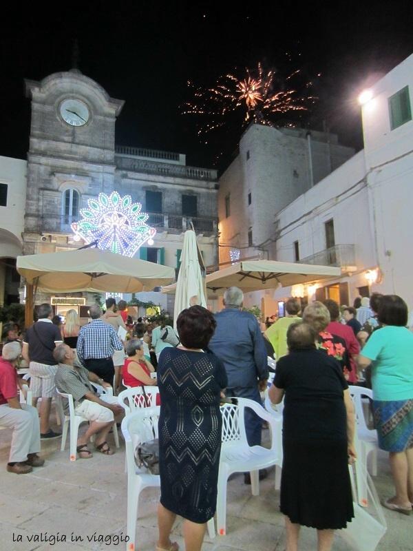 Piazza Vittorio Emanuele II con la Torre dell'Orologio, i fuochi d'artificio, l'aria di festa e la gente di Cisternino